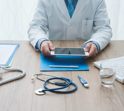 Professional doctor working at office desk, he is using a digital tablet, healthcare and technology concept